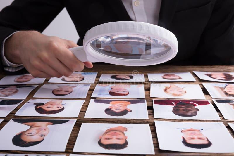 Esaminando la fotografia del ` s del candidato con la lente d'ingrandimento fotografia stock libera da diritti