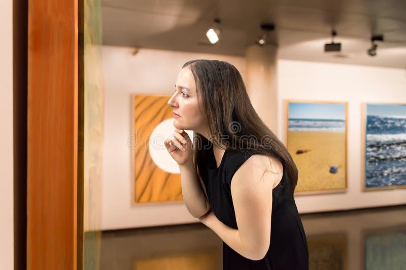 Esaminando un onn dell'opera d'arte il museo fotografia stock