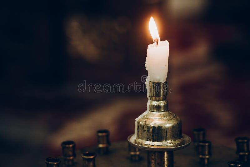 Esamini in controluce la luce, fiammeggiante sull'altare in chiesa cerimonia di nozze, santa fotografia stock