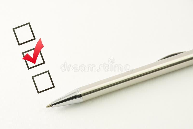 Esamini il modello, la scelta del questionario, casella di controllo contrassegnata con una penna su fondo di carta immagini stock