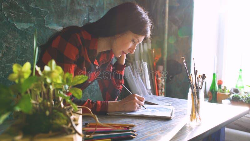 Esboço da pintura do artista da jovem mulher no caderno de papel com lápis Alargamento brilhante do sol da janela imagens de stock