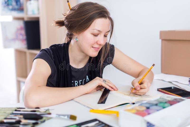 Esboço fêmea novo do desenho do artista usando o bloco de desenho com o lápis em seu local de trabalho no estúdio Retrato da vist foto de stock