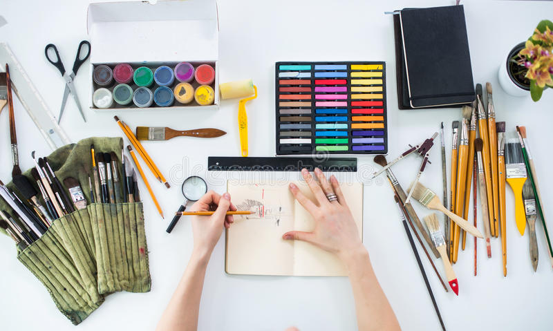 Esboço gráfico do desenho fêmea do artista no bloco de desenho com o lápis na galeria de arte, seu local de trabalho Foto da vist imagens de stock