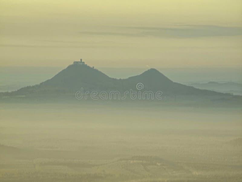 Esboços macios dos montes escondidos na névoa grossa, paisagem real vista obscura fotos de stock