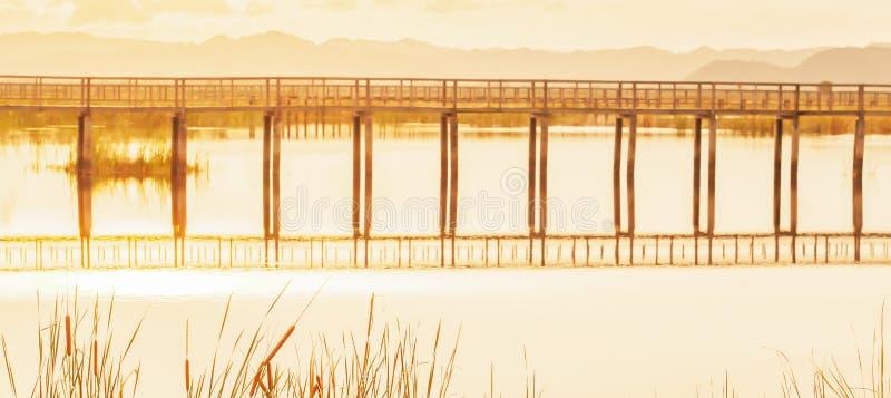 Esc?nico de la opini?n tropical del lago en la puesta del sol, el puente de madera abstracto reflej? en un lago, recubre con ca?a fotografía de archivo libre de regalías