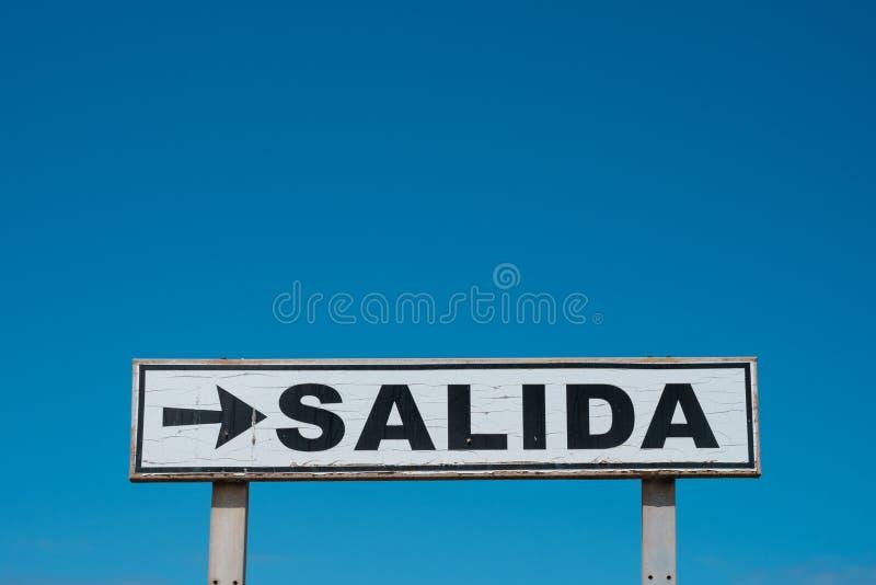 Esca lo Spagnolo del segno: SALIDA su cielo blu - fotografie stock libere da diritti