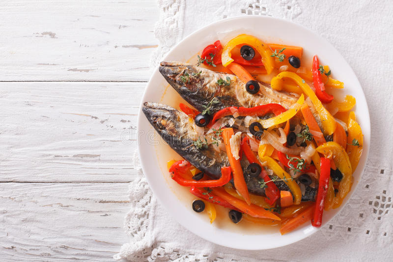 Escabeche fish: mackerel in vegetable marinade. horizontal top v. Escabeche fish: mackerel in vegetable marinade close-up on a plate on the table. horizontal stock photos