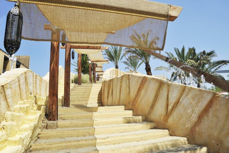 Escada ao ar livre com tenda solar. Ao fundo há palmeiras e jatos de água. Uma lâmpada árabe típica é fotografia de stock royalty free