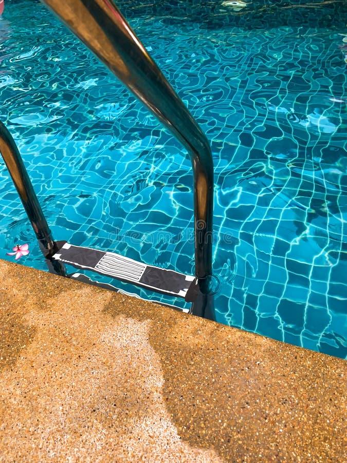 Escada das barras de garra na piscina azul fotografia de stock royalty free
