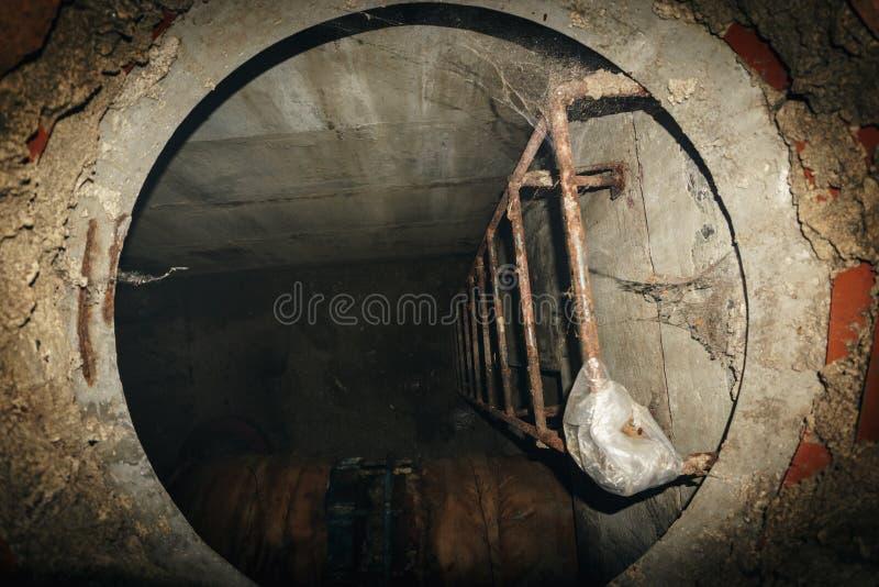 Escada de aço na descida técnica no sistema de água de esgoto subterrâneo, furo do esgoto fotos de stock royalty free