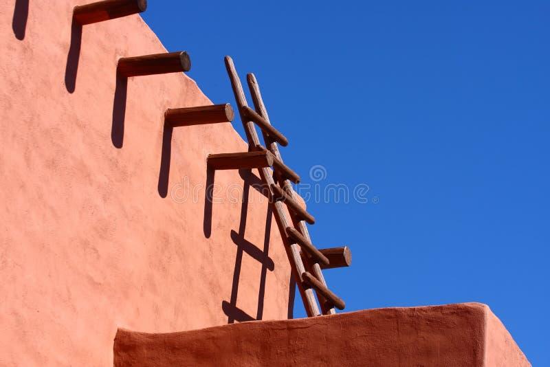 Escada de madeira na parede de Adobe fotografia de stock