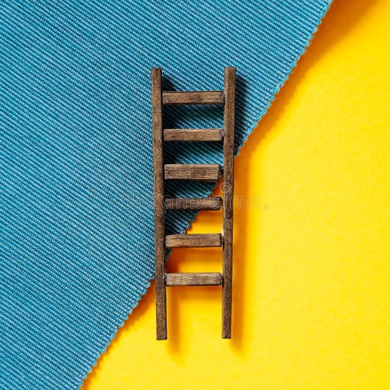 Escada de madeira no fundo amarelo e azul foto de stock