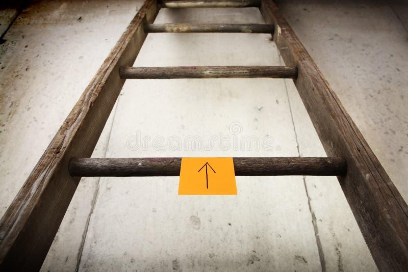 Escada de madeira velha em uma parede do cimento imagem de stock royalty free