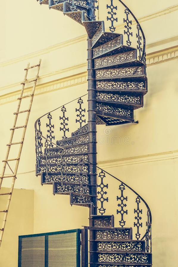 Escada espiral feita do escada do vintage e a de bambu na parede foto de stock royalty free