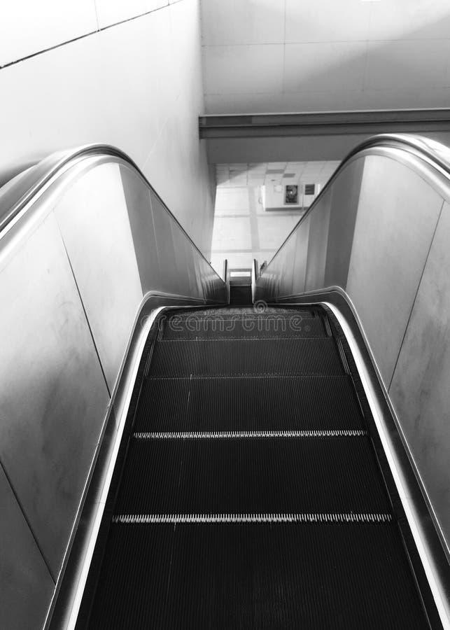 Escada rolante e escadaria na estação de metro preto e branco fotos de stock