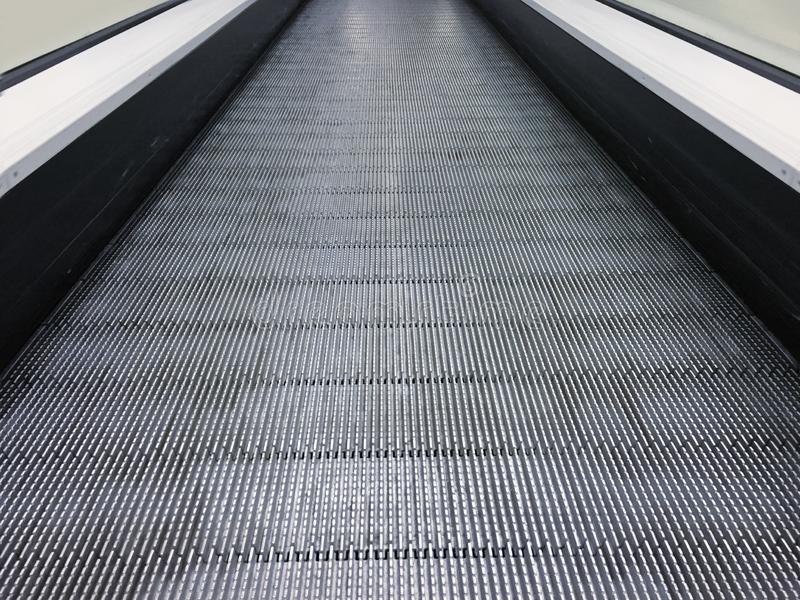 Escada rolante na alameda, no shopping ou no armazém da comunidade escadaria movente Luz de néon, escada rolante moderna fotografia de stock royalty free