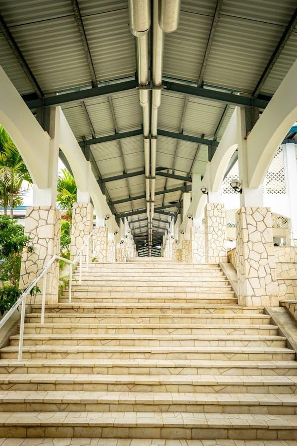 Escadaria ao longo do corredor exterior do corredor com teto alto, luzes e dispositivos elétricos acima e ao longo das colunas da fotografia de stock
