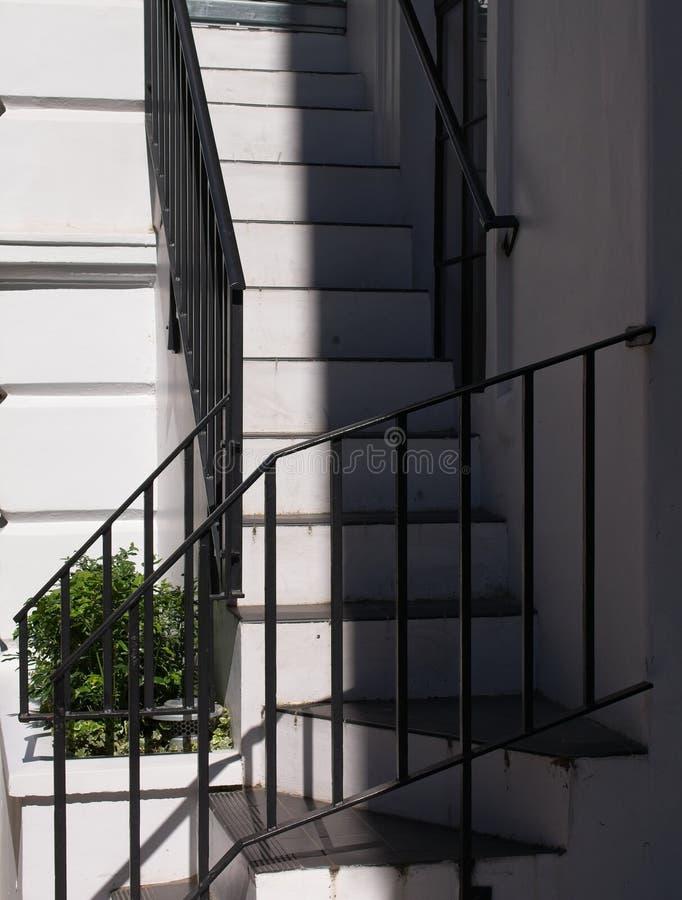 Escadaria branca com os corrimão pretos do ferro imagem de stock royalty free