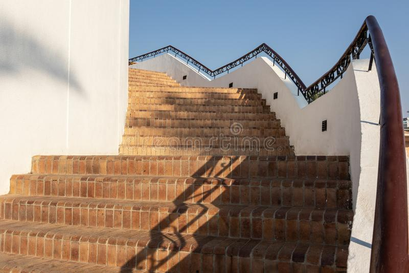 Escadaria com etapas do tijolo e trilhos de madeira com a decoração do metal contra a parede e o céu claro azul foto de stock
