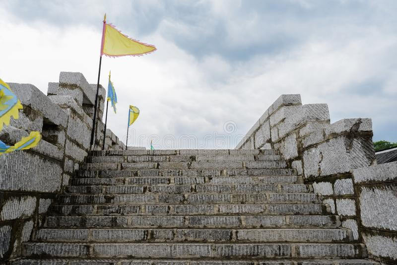 Escadaria da parede de pedra com parapeito e bandeiras no afterno nebuloso fotos de stock royalty free