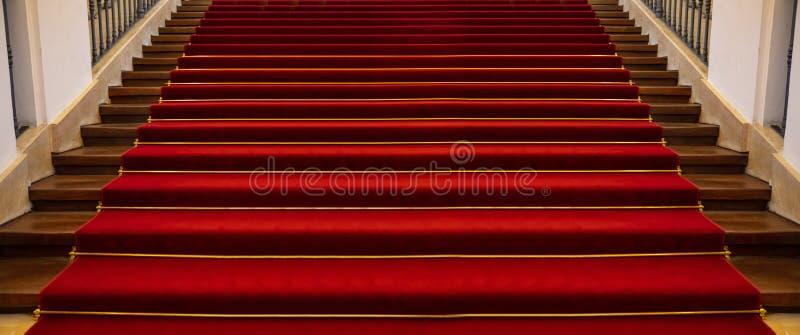 Escadaria de madeira coberta com o fundo do tapete vermelho fotografia de stock