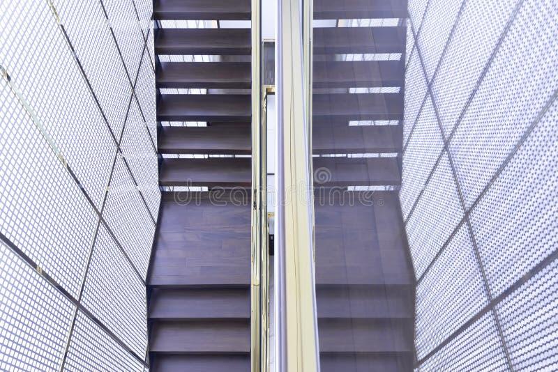 Escadaria de madeira luxuosa com o corrimão de vidro dos trilhos e do ouro no interior dourado da casa da grade fotos de stock royalty free