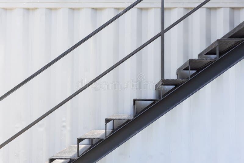 Escadaria do metal ou escada exterior da sa?da de emerg?ncia com fundo ondulado da parede da folha fotografia de stock royalty free
