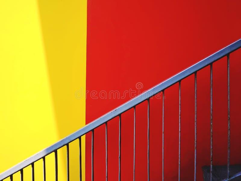 Escadaria e fundo vermelho e amarelo vívido da parede fotos de stock