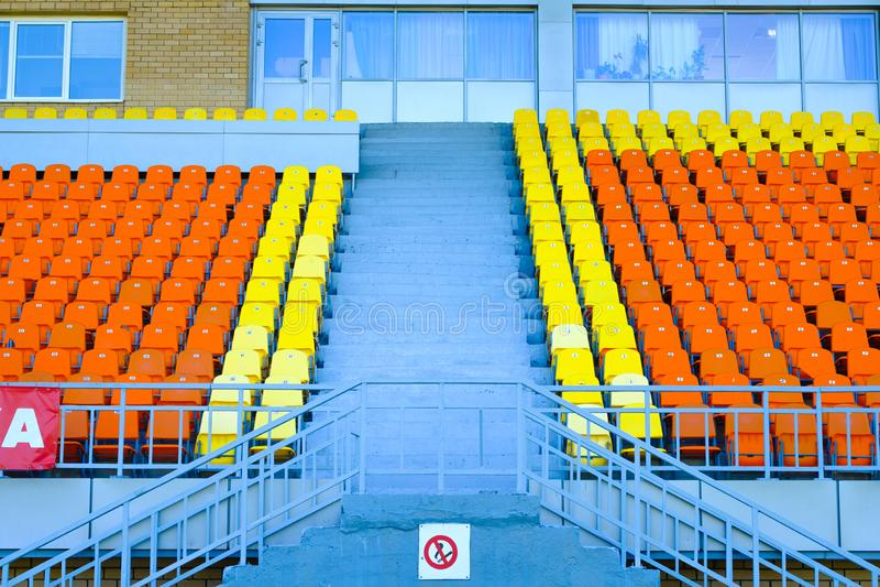 Escadaria e tribuna dos esportes de assentos alaranjados e amarelos fotos de stock