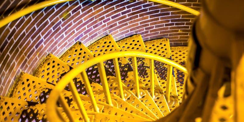 Escadaria espiral amarela com passos entrelaçados para baixo imagem de stock royalty free