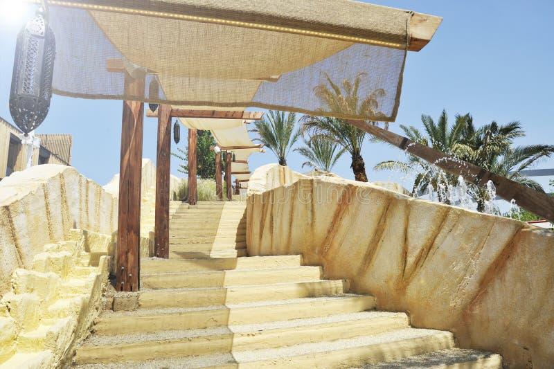 Escadaria exterior com uma barraca do sol No fundo há palmeiras e jatos da fonte da água Uma lâmpada árabe típica é imagens de stock royalty free