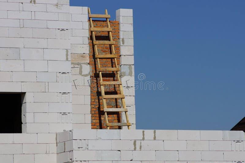 Escadaria marrom de madeira pela parede de tijolo cinzenta de uma casa inacabado contra o céu azul foto de stock royalty free