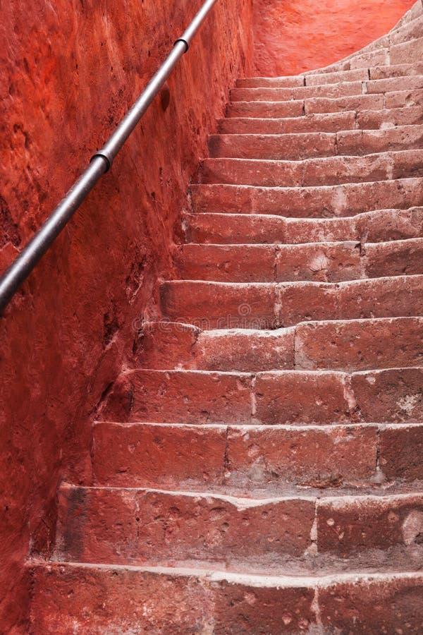 Escadaria velha e parede vermelha fotos de stock