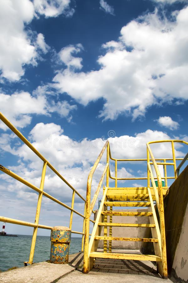 Escadas amarelas pela borda do oceano fotografia de stock