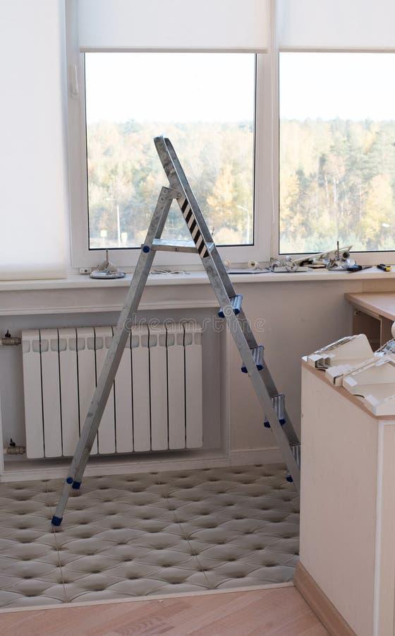 Escadas da escada port?til no apartamento pela janela na perspectiva dos materiais do reparo imagens de stock royalty free