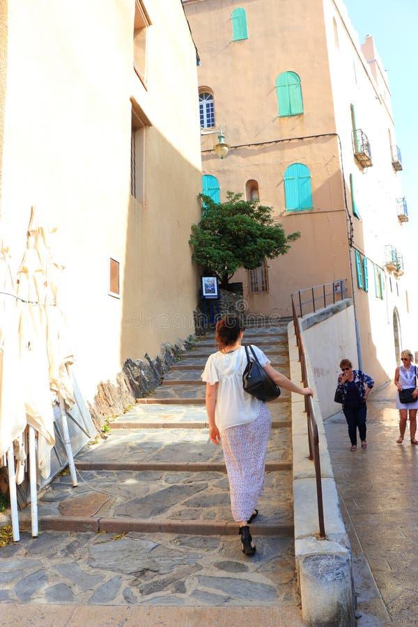 Escadas de escalada da mulher na cidade mediterrânea de Collioure, França imagens de stock