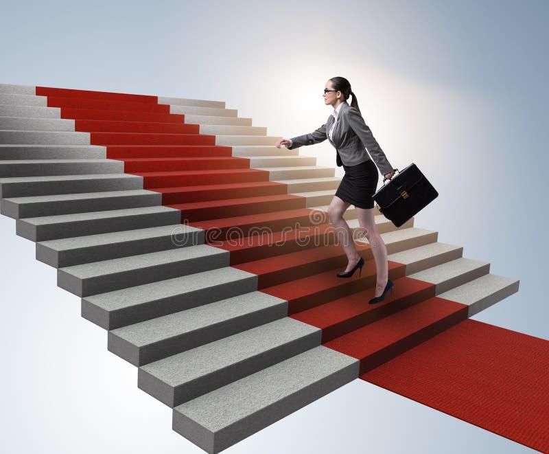 Escadas de escalada da mulher de neg?cios nova e tapete vermelho foto de stock