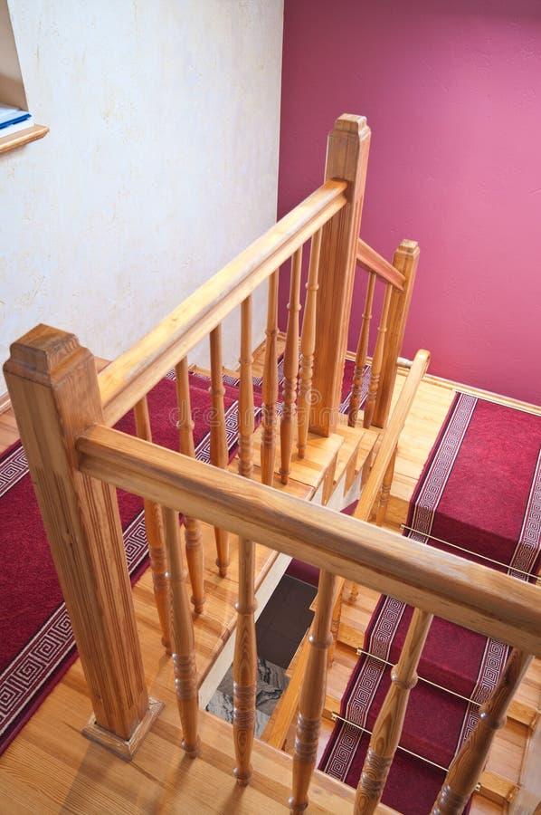 Escadas de madeira em uma casa com tapetes vermelhos imagem de stock royalty free