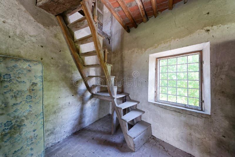 Escadas de madeira velhas na casa abandonada com janela fotografia de stock
