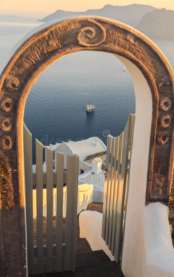 Escadas e portas contra a opinião dos navios, a ilha do caldera de Santorini, Grécia foto de stock royalty free