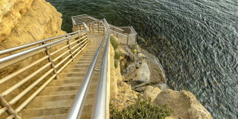 Escadas ensolarados em um penhasco que vai abaixo do oceano calmo fotos de stock
