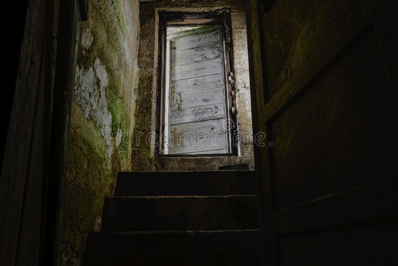 Escadas escuras com a porta velha e branca que conduz para baixo ao porão escuro foto de stock