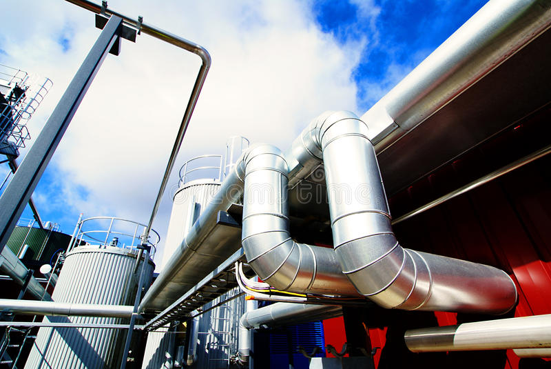 Escadas industriais dos tanques de aço de encontro ao céu azul fotos de stock royalty free