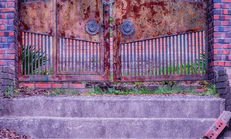 Escadas que conduzem à porta oxidada fechado fotografia de stock