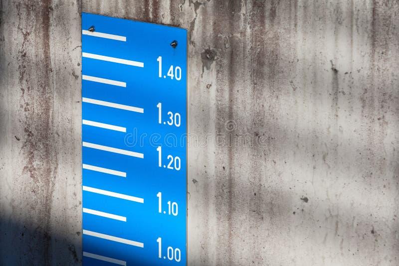 Escala azul da medida do nível da maré no muro de cimento imagem de stock royalty free