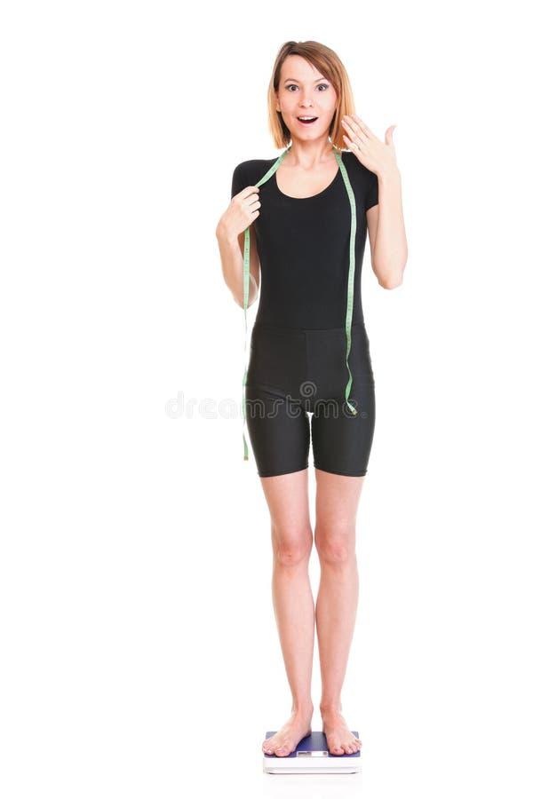 A escala caucasiano do peso da jovem mulher que olha a câmera isolou o branco imagem de stock