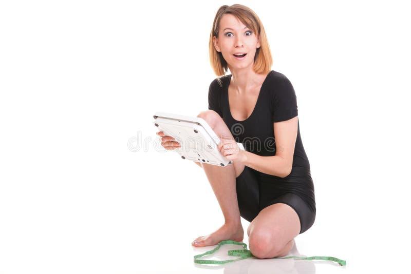 Escala caucasiano do peso da jovem mulher que olha o branco da câmera fotos de stock royalty free