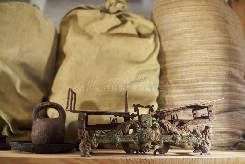 Escala clássica velha do comércio do vintage na tabela de madeira com os sacos no fundo imagem de stock