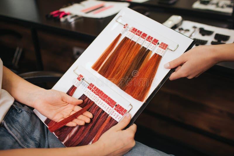 Escala de cores do cabelo no salão de beleza Cliente fêmea com o cabeleireiro que escolhe o cabelo da cor das amostras da paleta  imagem de stock