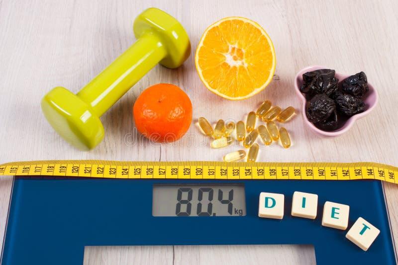 Escala de Digitaces con la cinta métrica, pesas de gimnasia, tabletas, frutas, adelgazando concepto foto de archivo